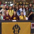 Anni Scholl (seated, center) signed a letter of intent Tuesday to play basketball for MSU. Scholl is surround by her Henrietta Lady Cat teammates and Coach Danielle Hensley.