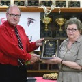 Midway ISD Supt. Hollis Adams presents a plaque of recognition to Judy Peden during a retirement reception Tuesday.